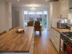 Laminate walnut effect worktops compliments the timber flooring on this project by Purple Kitchens - http://www.sncollection.co.uk/real-kitchens/real-kitchen-projects/langham-painted-purple-kitchens.html