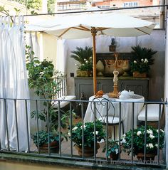 An elegant outdoor dining area beneath a white parasol on a tiled roof terrace that has curtains for additional privacy