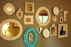 My mirror collage.  Every.single.thing. on this wall was  bought at either thrift stores or garage sales!  Once again, they were all different colors  when I bought them, and then  spray painted them all the same color.  Even though the collage was  primarily mirrors, I didn't want the  entire thing  to be so predictable.  So, I added a plate here, an initial there...  just to mix it up a bit!