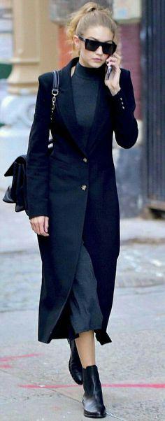 Gigi Hadid a turtleneck, midi skirt/dress, and long coat.