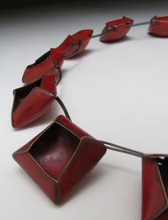 Kim Lucci Elbualy -Description: Red Elements: cut, raised back, fold-formed, torch-fired enamel patina Mechanism & Cable: fabricated sterling silver, silver cable