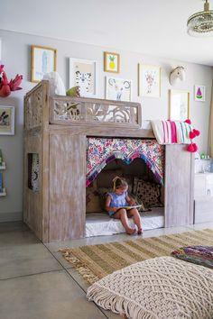Cuarto de niña con cama en petiribí (Mesopotamia) diseñada alrededor de un tapiz de India, con alfombra de yute y lúrex, y pufs de macramé.