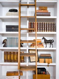 Designer Emily Henderson gives these bookshelves a timeless English-library feel by grouping similarly bound books and mixing in a few old cigar boxes and vintage finds, like a rotary dial telephone, brass eagle bookends and a bronze horse. An antique library ladder, leaned against the bookcase, isn't functional but adds to the look.