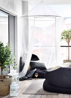 Ein Balkon mit RISÖ Sitzsäcken für draußen in Schwarz unter einem Moskitonetz