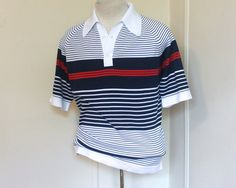 this old man vintage presents ... super preppy polo shirt from the 1980s ... still with the original hang tag. NEVER WORN! 2 buttons up the front. pointy collar. raglan sleeves. red + white + blue stripes!  tagged ... Thane Tycora Full Fashioned 80% dacron polyester 20% olefin made in USA  measurements ... vintage size: large chest, armpit to armpit: 23 waist: 21.5 sleeve, armpit to sleeve cuff: 6 length, base of collar down the back: 28.5 measurements are taken flat from resting point to…