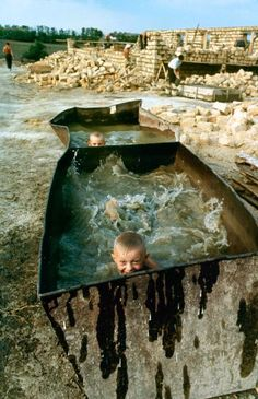 <b>Caption from LIFE.</b> While students work, farm boys cool off in the plasterers' water trough.