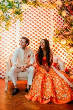 Candid Couple Shot - Filip & Tuhina wedding story | WedMeGood | Bride in a Orange and Gold Lehenga and Groom in a White Sherwani  #wedmegood #indianbride #indianwedding #bridal #candidcoupleshot #candidcouple #sherwani #lehenga