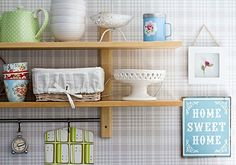 Two-toned wallpaper adds visual interest to these open kitchen shelves. Other thoughts: colored tile or beadboard.