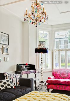 "The colorful chandelier pulls the look together, from the Vintage Chandelier Company. The bespoke ottoman was another investment buy. The designer Berger is a believer in mixing things up. ""I love to include investment items with cheap buys from the Internet, It creates a much more eclectic look & it's nice when different patterns clash."" The walls are kept neutral  using Dulux paint in Timeless to create the look. The black sofa is from BoConcept."