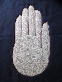 Trapunto with applique by Nina Paley.  The pattern on the hand is based on mehendi, the spirally flames on Tibetan art