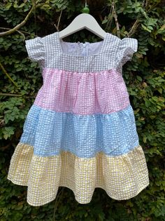 Pretty layers of grey, pink, blue and yellow gives a visual rainbow like look to the pretty sleeveless gingham summer dress. An easy to use zip is at the back of the dress that helps in getting your baby's dress out for a shower in a breeze. The dress is made from cotton seersucker fabric. Dress Out, Dress Skirt, Pink Blue, Yellow, Summer Picnic, Cute Baby Clothes, Baby Shop, Seersucker, Little Babies