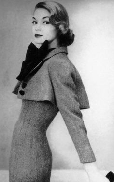 1951 Jean Patchett in wasp-waisted dress with tiny fly-away bolero worn with butterfly-bow silk blouse by Norell, photo by John Rawlings