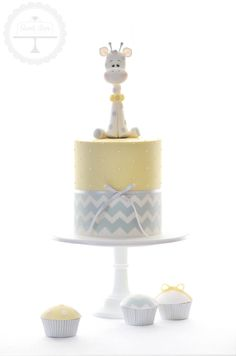 Cuteness overload for this baby shower cake with hand-modelled giraffe topper and matching cupcakes