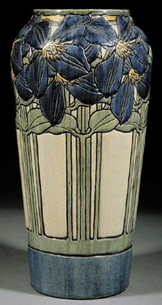 "Newcomb College Pottery: Decorated by Marie de Hoa LeBlanc, with an incised design of jackmanii climbing clematis in blue, green and yellow underglaze, the base was marked with Newcomb cipher, decorator's mark, Joseph Meyer's potter's mark, ""Q"" for buff clay body and reg. no. ""VV19."" The vase stands 13 inches high and is 6½ inches in diameter."