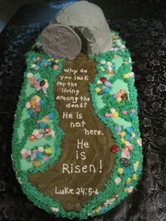 "He is Risen! - Buttercream iced cake, with white chocolate ""stone,"" Chocolate rocks.  The cake was made from one square, a round cut in half for each end and small cakes carved to make the tomb.  Flowers are buttercream."