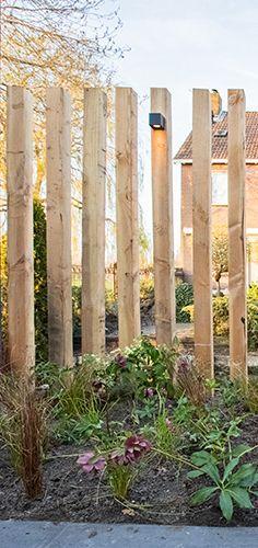 In deze tuin is rekening gehouden met alle wensen van Ivar en Margret. Met deze lamellenwand behoudt het stel toch het mooie uitzicht en hebben ze meer privacy. En het allerbelangrijkste is natuurlijk dat ze hun zoon James met een gerust hart in de tuin kunnen laten spelen op het grasveldje. Zij kunnen vanaf het terras aan het huis genieten van hem en de prachtige tuin. De pergola in dezelfde kleur verbindt de lamellenwand, met de tuinopslag en het fijnste plekje; de loungeplek aan het…
