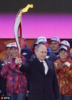Russian President Vladimir Putin holds the torch with Olympic flame, 10/6/13.