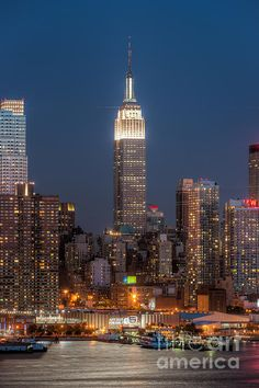 The Empire State Building and surrounding buildings at dusk, with the Hudson River lit by the light of the full moon, as seen from Weehawken, New Jersey. New York City NYC. Clarence Holmes