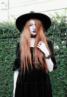 Olivia Emily wears Asos Reclaimed Vintage tiered black velvet dress, Killstar Witch Brim hat, and Kiki Minchin Classic Cross silver necklace