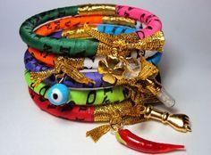 Conjunto com 5 pulseiras forradas com fita do bonfim coloridas e pingentes patuá: pimenta, sal grosso, trevo, figa e olho grego.