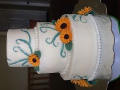 Sunflower wedding cake. Lemon cake with lemon Swiss meringue buttercream and fresh blueberries, covered in homemade fondant with hand painted details and modeling chocolate sunflowers and leaves.