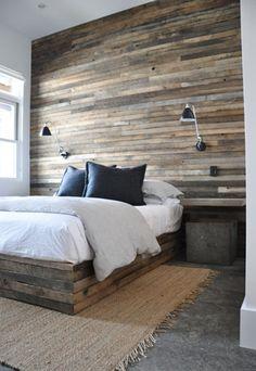Scandinavinsch: licht, wit, zwart, grijs, hout, natuurlijke materialen - Slaapkamer met betonvloer met sisalkleed en houten achterwand en bedombouw.
