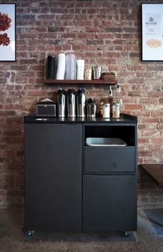 A custom designed condiment bar houses condiments for coffee as well as a bus bin and trash bin. Jane Kim Design