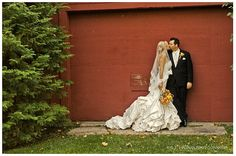 An old red barn serves as backdrop for this wedding photo.