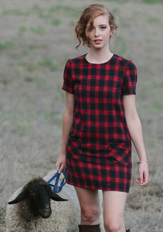 We adore this preppy shift dress designed with an allover plaid print in classic hues of red, black, and blue. It's complete with two front pockets, short sleeves, and a back keyhole cuto...