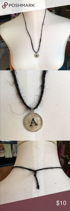 NEW! Handmade Black/Beige 'A' Initial Necklace Beautiful, handmade black twine necklace featuring a silver-coated beige pendant with the initial 'A' in the center. Approx. 12 inches long, including pendant. Only one available. Handmade Jewelry Necklaces