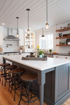 Farmhouse kitchen with shiplap plank ceiling and beadboard island painted in a…