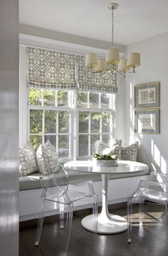 Gray breakfast nook, white trim, lucite chairs, built in bench
