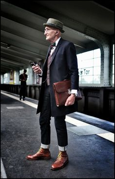 Pants rolled w shoes is a crisp look w boots. Just enough detailing shown w leather. Long jacket is fresh. Remove bow tie and vest likely. No hat