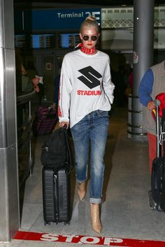 Karlie Kloss wearing Stella McCartney Black Falabella Go Backpack, Away the Carry-on Suitcase in Black and Louis Vuitton X Supreme Scarf