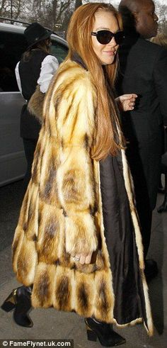 Lindsey Lohan fur hag.  Fur hags are all so ugly.  They wear oversized dead animal coats and look like utter assclowns.  I've never seen anyone who looks good in fur.  Arrogant assholes can't even see how stupid they look.