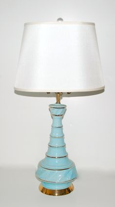 "Tiffany Blue Lamp: 1950's Tiffany blue cylinder lamp with gold accents.  We see Holly Golightly at her bedroom writing desk now.    8""Diameter x 31""High"