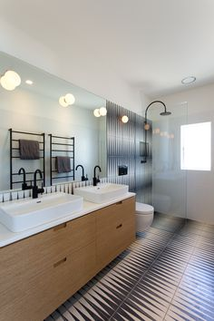 Handmade black-and-white tiles in the bathroom provide a striking counterpoint to the fine detailing of joinery throughout the apartment. Bathroom Wall, Master Bathroom, Bathroom Lighting, Black And White Tiles, Maker, Bathroom Inspiration, Modern Design, House Design, Furniture
