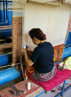 A woman works on a large carpet weaving loom in Kashgar.