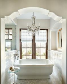 An arched doorway leads to an ethereal bathroom nook filled with a freestanding bathtub and a vintage tub filler placed atop a marble hex tiled floor flanked by a glass and marble shower to the left and an arched gold beaded mirror to the right.