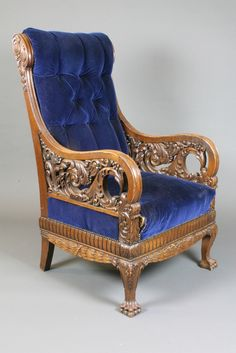 A late 19th Century carved oak library chair having foliate and scroll carved decoration, blue buttoned velvet upholstery, the base decorated with laurel and raised on braganza feet £150-250