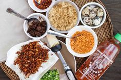 Ingredients to make Banh Trang Nuong: Scallion oil, Sriracha Sauce, toasted dried shrimp, quail eggs, pork floss (dried pork), sate sauce, fermented shrimp paste (Mam Ruoc), and fried shallots.
