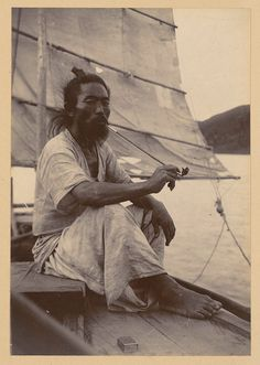 Title: Korean boatman  Date: ca. 1904  Place: Asia: South Korea  Type: Portraits  Description: Korean sailor takes a break from trasporting cargo and people, sitting under the shadow from the sail, smoking from his long bamboo pipe. He wears cool hemp clothes.