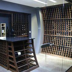 Équilibrée entre ses supports de bois et sa station de dégustation en quartz noir, cette cave à vin rappelle les fûts servant au vieillissement du vin.