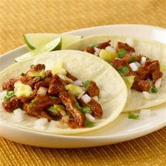 Quickly whip up authentic Mexican tacos made of thinly sliced, spicy marinated pork served on warm corn tortillas with lime, finely chopped onion, cilantro and pineapple.