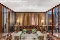 A recepção, com sofás em veludo, cortinas em tafetá de seda, mesa de centro em vidro (Perfil Casa) e lustre em alabrasto com bronze