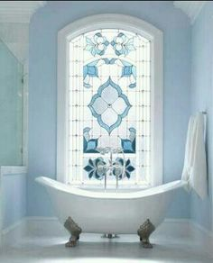 Beautiful stain glass window and awesome claw foot bathtub.