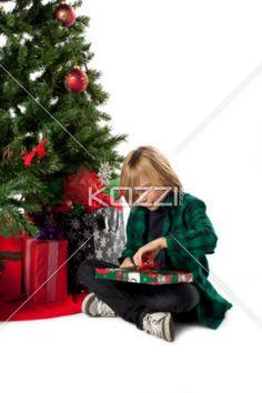 boy unpacking christmas present. - Blonde boy in green shirt, unpacks a christmas present beside a Christmas Tree on a White Background. Model: Josh Chapman