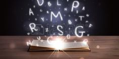 Open book with glowing letters flying out on wood deck photo