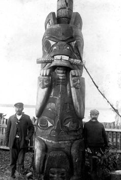 This pole once stood at the rear of the Monster House. The pole represented Chief Wiah's crest of a standing beaver with potlatch rings and the crest of a sculpin prominently displayed on its abdomen.<br><br>Harry Wiah, son of Chief Wiah, stands on the left.