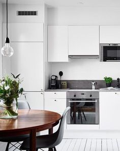 love the dark polished wood table in a white kitchen